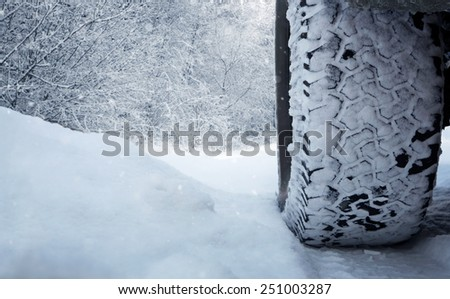 Close up of car tire in the snow with copy space - stock photo