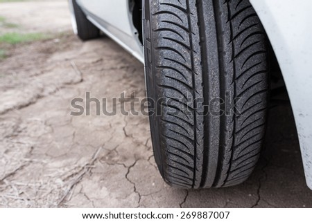 Close up of car tyre on cracked earth surface - stock photo