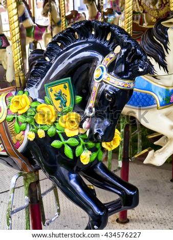 Close-up of carousel horse; black stallion head on funfair roundabout  - stock photo