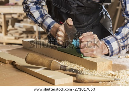 Close up of carpenter hands working with plane in his studio - stock photo