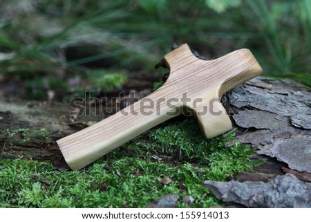 Close up of carved cross on a green tree  - stock photo