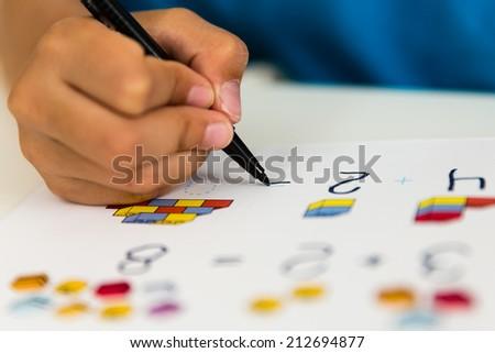 Close-up of caucasian boy doing his elementary school homework. - stock photo