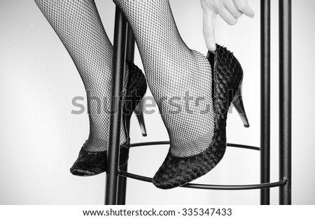 Close up of Caucasian woman in fishnet stockings, black and white toned image - stock photo