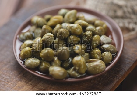 Close-up of ceramic saucer with marinated capers, rustic wooden background - stock photo