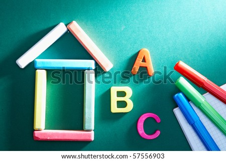 Close-up of chalk house, letters and highlighters on blackboard - stock photo