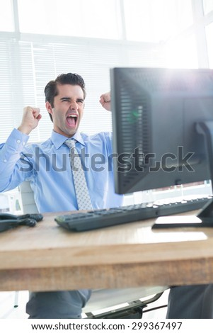 Close up of cheerful businessman cheering in the office - stock photo