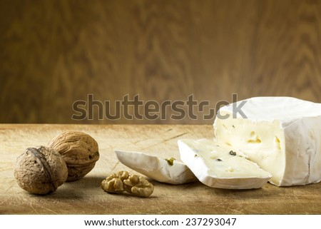 Close-up of cheese and walnuts on wood background - stock photo