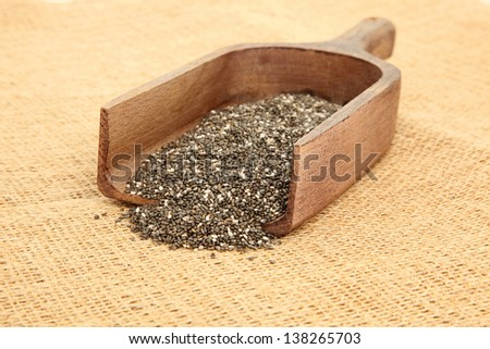 Close Up Of Chia Seeds In Wooden Scoop On Burlap Bag - stock photo
