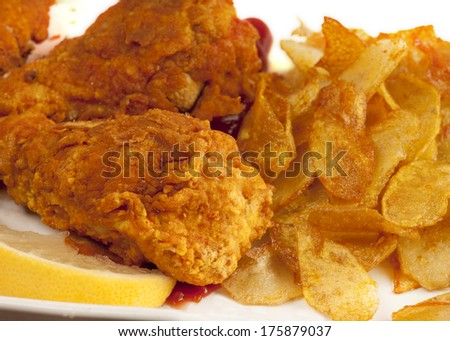 Close up of chicken drumsticks marinated in chili sauce then deep fried in oatmeal batter, giving a thick, crunchy covering.  Served with potato crisps and tomato sauce, garnished with a lemon slice - stock photo