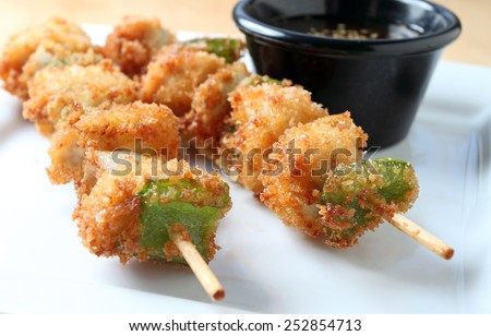 Close up of chicken kushi sticks or chicken skewers on plate with dipping sauce. - stock photo