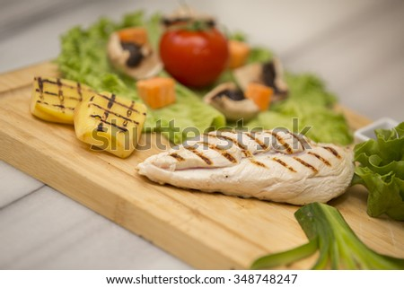 Close up of chiken BBQ with peppers and lettuce. Grilled steaks, baked potatoes and vegetables.  - stock photo