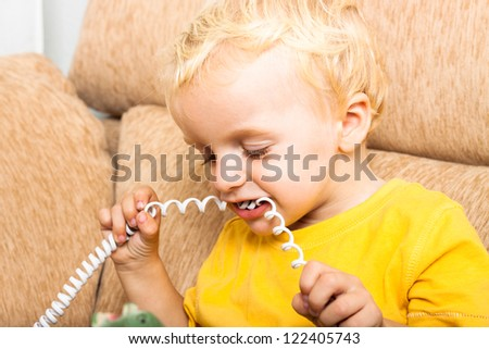 Close up of child boy biting phone wire. - stock photo