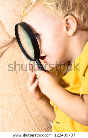 Close up of child boy exploring magnifying glass. - stock photo
