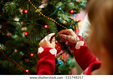 Close-up of child hanging decorative toy ball on Christmas tree branch - stock photo