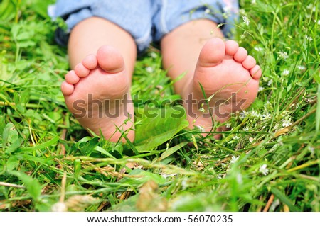close up of child's feet on the green grass - stock photo