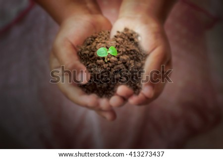 Close-up of child's hands holding dirt  - stock photo