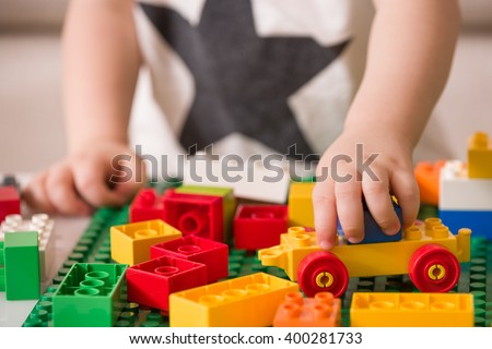 Close up of child's hands playing with colorful plastic bricks at the table. Toddler having fun and building out of bright constructor bricks. Early learning.  stripe background. Developing toys - stock photo