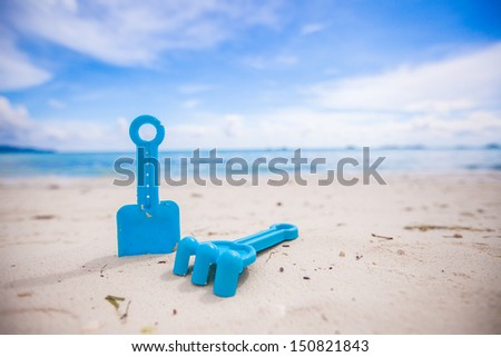 close-up of children's toys on a white beach - stock photo