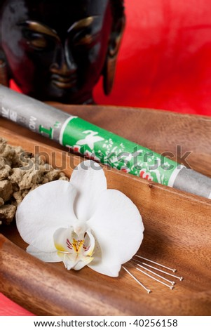 Close up of chinese medicine tools, needles, moxa and an orchid flower - stock photo