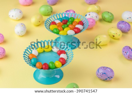 Close up of chocolate candy eggs and jelly beans in cupcake stands on pastel background. - stock photo