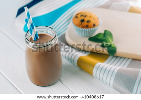 Close up of chocolate milk in glass bottle with blue striped straw on white wooden background. Selective focus - stock photo