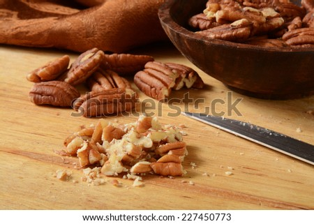 close up of chopped pecans on a cutting board  - stock photo