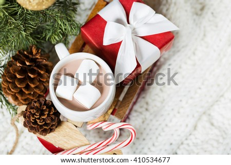 close-up of christmas time themed decorations by the tree: toy sled with hot chocolate filled cup and marshmallows, wrapped present, candy canes and tree cones, cozy knitted throw in the background - stock photo