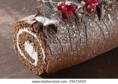 Close up of Christmas Yule chocolate log decorated with dipped holly leaves and berries, dusted with icing sugar - stock photo