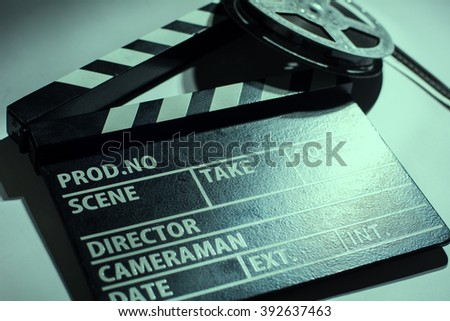 Close-up of cinema clap and film reel with. Background for movie shooting advertising - stock photo