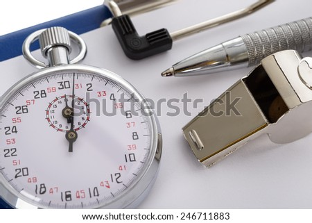 Close-up Of Clipboard With Whistle; Pen; Paper And Stopwatch On White Background - stock photo