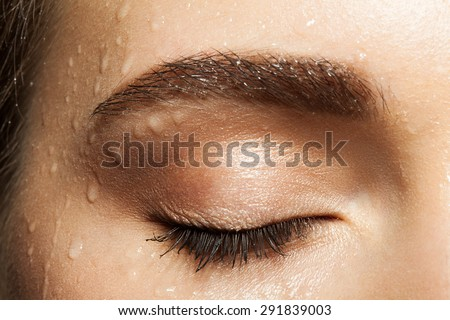 Close-up of closed eye with long eyelashes and eyebrows brown with water drops - stock photo