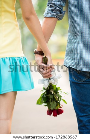 Close-up of clutched hands of two lovers with bouquet  - stock photo