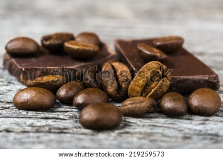 close up of coffee beans and  chocolate on gray wooden background - stock photo