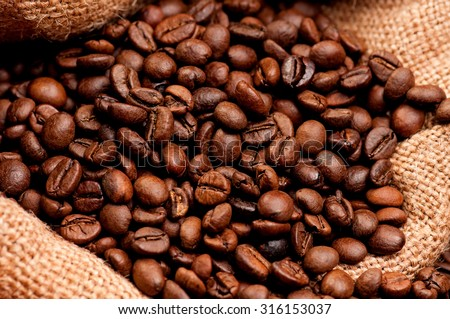 Close up of coffee beans in burlap sack - stock photo