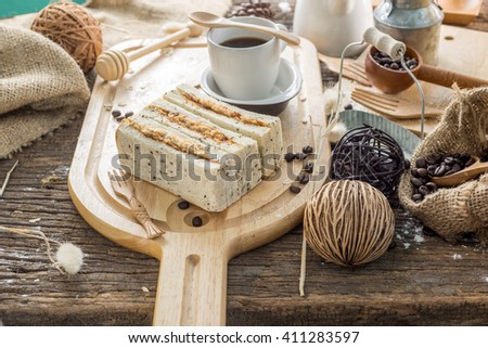 Close up of coffee cup and freshly baked bread with flour on a wooden table top - stock photo