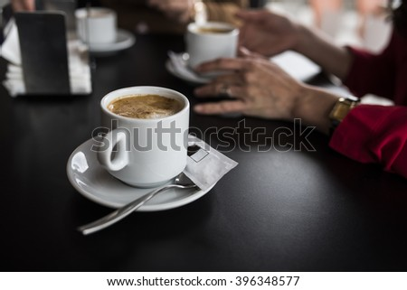 Close-up of coffee cup on plate on dark wooden table in cafe. Unrecognizable woman sitting at table on background  - stock photo