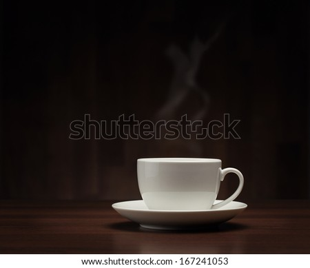 Close up of coffee cup on the table over dark background with copy space - stock photo