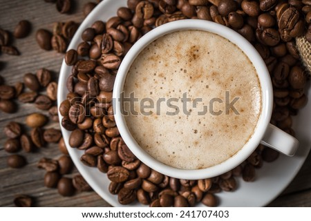 Close-up of coffee cup with roasted coffee beans on wooden background. View from top  - stock photo