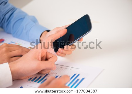 Close-up of colleagues using smartphone - stock photo