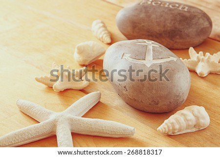 Close up of collection of nautical and beach objects over wooden background - stock photo