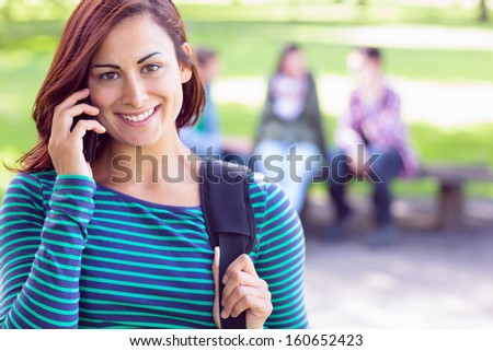 Close-up of college girl using mobile phone with blurred students sitting in the park - stock photo