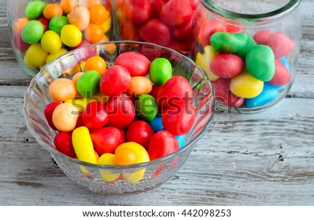 Close-up of colorful bright sweets in glass bowls on wooden table - stock photo