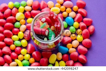 Close-up of colorful candies and jar with liquorice.From above - stock photo