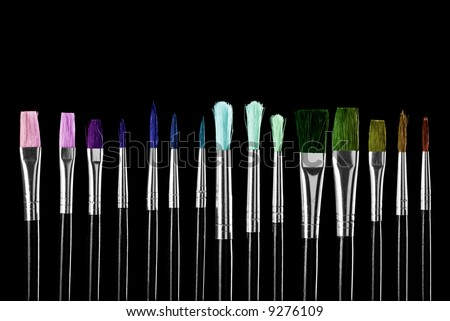Close-up of colorful paintbrushes against black background. - stock photo