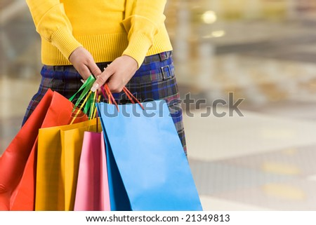 Close-up of colorful paperbags being held by female in the shopping center - stock photo