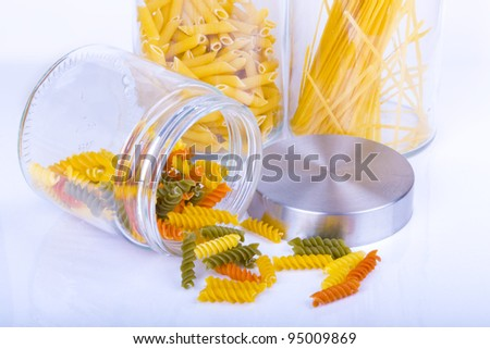 Close up of colorful rotini, penne, and spaghetti pasta in a glass jar isolated on white background - stock photo