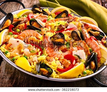 Close Up of Colorful Seafood Spanish Paella Rice Dish with Shrimp and Mussels Shellfish Garnished with Fresh Lemon and Served in Pan with Green Linen Napkin on Rustic Wooden Table - stock photo
