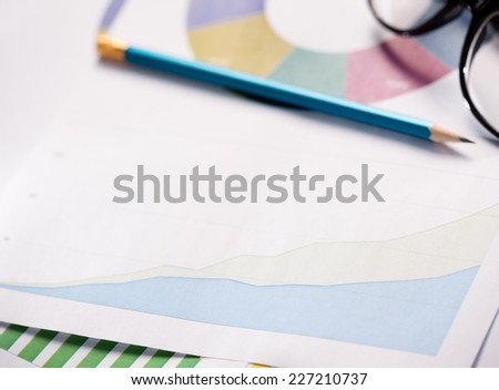 Close up of colourful graphs and calculator. - stock photo