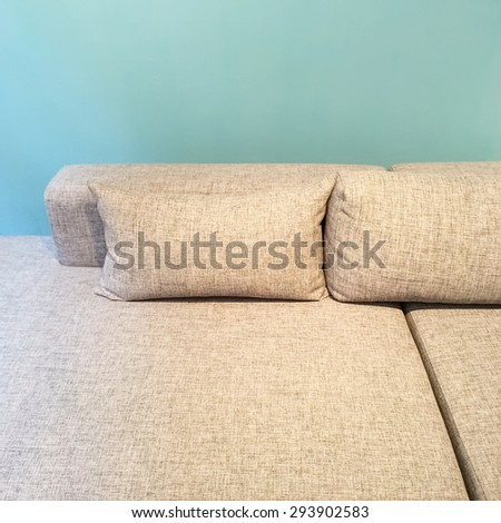 Close-up of comfortable sofa with cushions near green wall. - stock photo