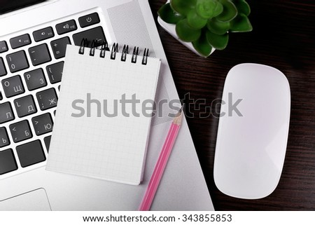 Close-up of comfortable working place on black wooden background, top view - stock photo